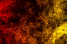 Abstract Art Colored Yellow And Orange  Smoke On Black Isolated Background. Stop The Movement Of Mul
