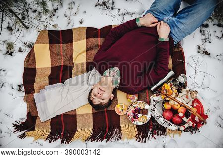 A Young Alone Man Or Boy Is Lying On A Blanket At The Winter Picnic On The Valentines Day In A Snowy
