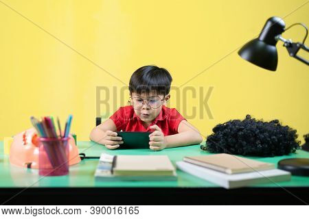 Boy Playing Smart Phone Games, Angry Expression, At His Desk.