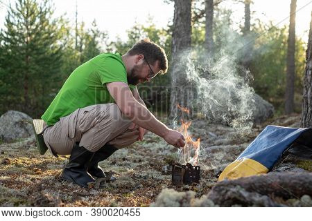 Man In Hiking Clothes Heats A Metal Prefabricated Burner With Wood, For Cooking, In The Forest, In A