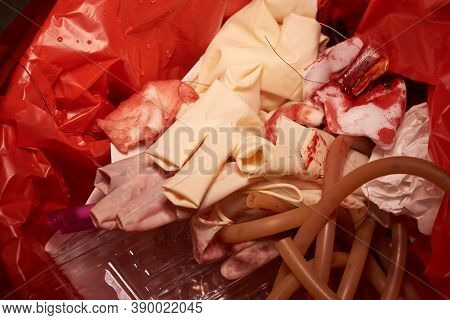 Close-up View Of Disposable Gloves, Blood Stained Gauzes , Sutures And Suctionafter Surgery In Red G