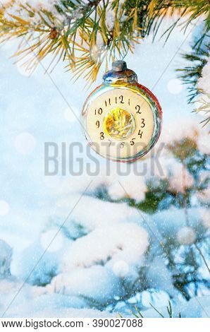 New Year card, New Year background, New Year glass Christmas toy in the form of clock showing the New Year Eve, on snowy fir tree. New Year postcard with New year toy