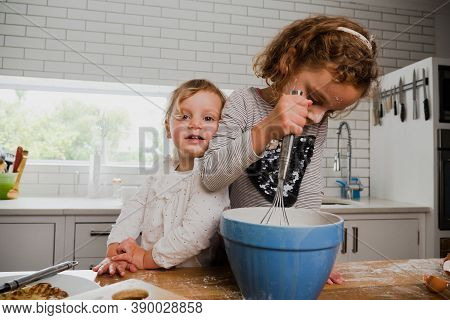 Two Smiling Siblings Baking Together In Kitchen.