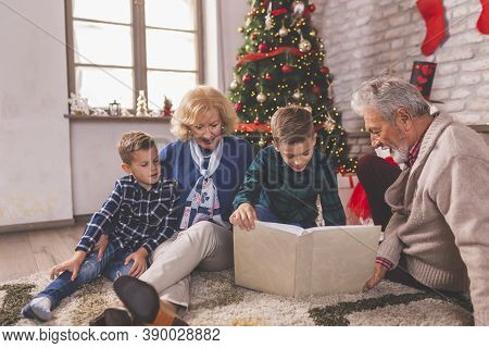 Happy Family Celebrating Christmas Together At Home, Children Playing With Their Grandparents By Nic