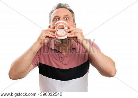 Joking Adult Man Model Presenting Close-up Of Fake Teeth Denture Prothesis As Funny Concept Covering
