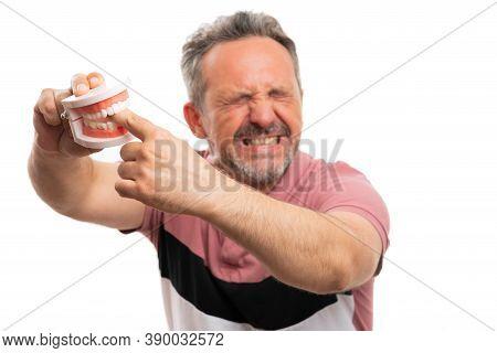 Close-up Of Fake Dentures Teeth Biting Hurt Expression Adult Male Model Index Finger Wearing Summer