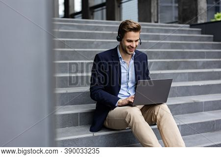 Portrait Of Handsome Smiling Man In Casual Wear Sitting On Bench Using Laptop For Online Meeting, Vi
