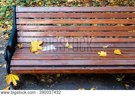 Thrown Medical Face Fask On Wooden Bench In City Park On Autumn Day