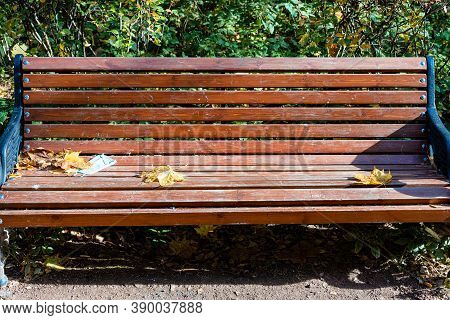 Front View Of Wooden Bench With Used Medical Face Mask And Yellow Fallen Maple Leaves In City Park O
