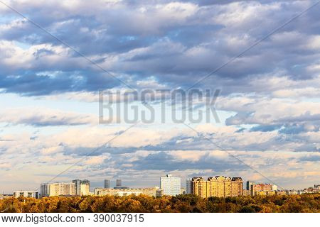 Blue Sky With Low Dark Blue Clouds Over Urban Park And Residential District On Horizon Lit By Autumn