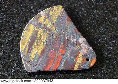 Pendant From Polished Jaspillite (jaspilite) Stone On Black Granite Background