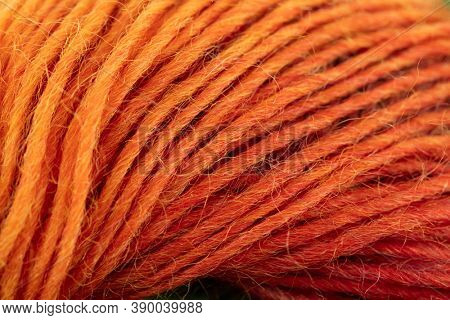Warm orange to red wool yarn abstract macro.