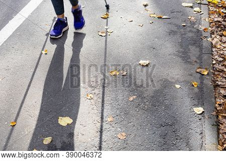 Legs And Shadow Of Walker Of Nordic Walking On Pathway In City Park On Sunny Autumn Day