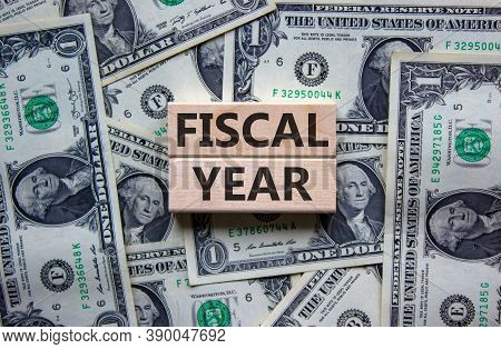 Concept Words 'fiscal Year' On Wooden Blocks On A Beautiful Background From Dollar Bills. Business C
