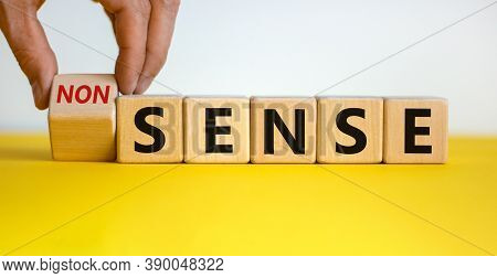 Hand Flips A Cube And Changes The Word 'nonsense' To 'sense' Or Vice Versa. Beautiful Yellow Table,