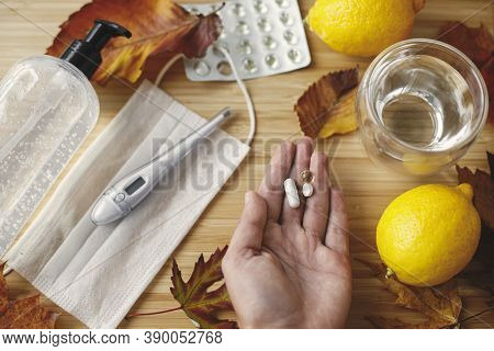 Vitamin D, C And Zinc Pills In Hand On Background Of Fall Leaves, Face Mask, Sanitizer, Lemons