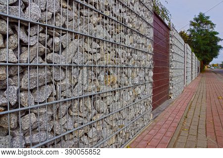 Gabions. A Fragment Of A Fence Made Of Gabions. Separation Of The Street From Residential Areas.