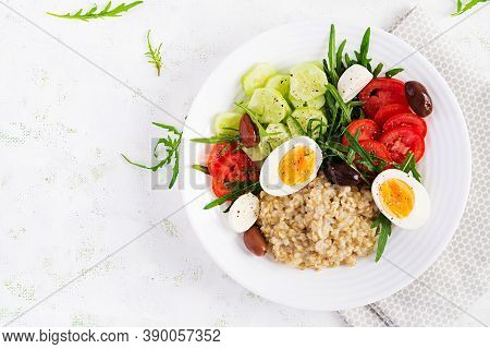 Breakfast Oatmeal Porridge With Greek Salad Of Tomatoes, Cucumbers, Olives And Eggs. Healthy Balance