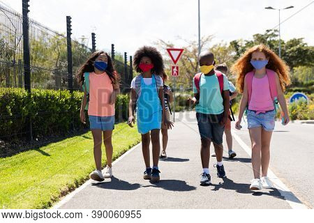 Multi ethnic group of school children wearing face masks, walking on the street. Education back to school health safety during Covid19 Coronavirus pandemic.