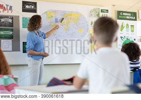 Caucasian female teacher wearing face mask at school, teaching children at school classroom. Education back to school health safety during Covid19 Coronavirus pandemic.