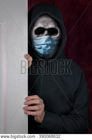 Stalker Or Burglar Entering A Home Through Doorway With Wearing A Human Skull Fitted With Medical Fa