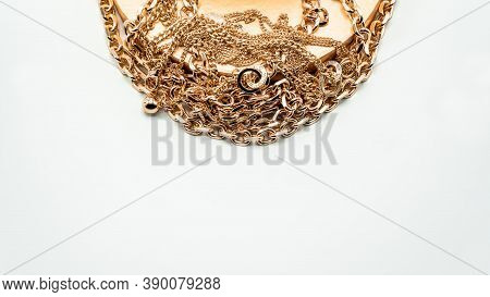 Bijouterie. Gold Chains And A Beautiful Golden Box On A White Background. Jewelry Concept