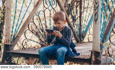 Focused Boy Using Smartphone In Park. Serious Concentrated School Aged Boy In Casual Wear Sitting On
