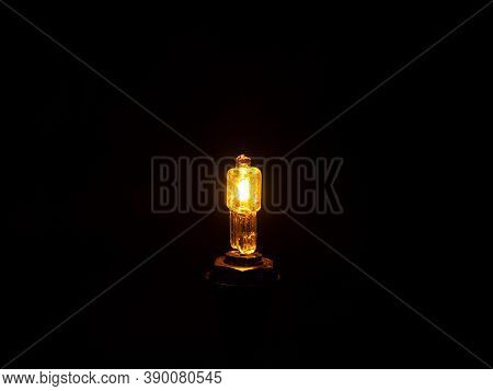 Glow Of A Halogen Bulb In The Dark. Light Of An Electric Halogen Bulb In The Dark. Electric Light So