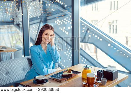 Enthusiastic Woman In Trendy Autumn Outfit Chilling In Cozy Cafe, Adjusting Hair, Happy Emotions. Tr