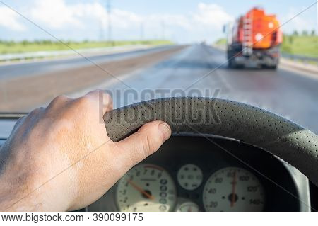 View Of The Driver Hand On The Steering Wheel Of A Car That Makes A Careful Overtaking Of A Fuel Tan