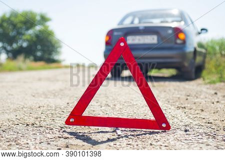Red Warning Triangle With A Broken Down Car. A Car With A Breakdown Alongside The Road.