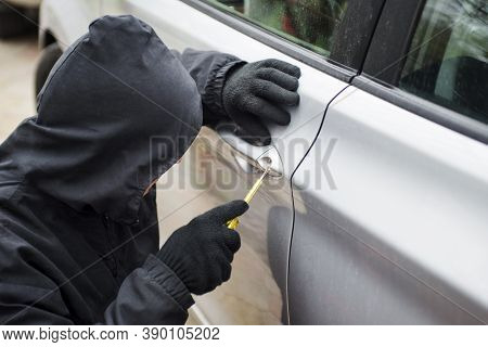 Car Thief In Action. Thief Stealing Automobile Car. The Man Dressed In Black Trying To Break Into Th