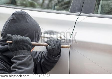 Male Thief Going To Break Car Window With Crowbar. Car Theft - Thief Trying To Break Into The Vehicl