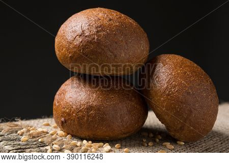 Three Rolls Of Dark Bread On A Wooden Board With Wheat Grains, Black Background