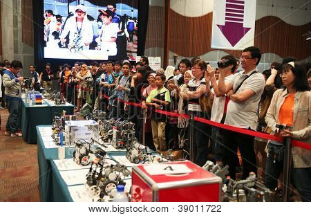 SUBANG JAYA - NOV 10: Unidentified visitors and supporters cheer their team on at the World Robot Olympaid on November 10, 2012 in Subang Jaya, Malaysia. This year's theme is Robots connecting people.