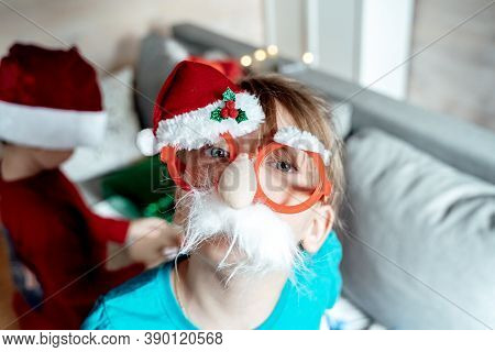Little Cute Girl In Funny Glasses With Nose, Red Christmas Santa Claus Hat. Congratulations,greeting