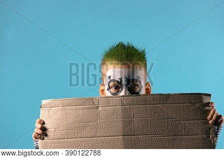 Discouraged Child Holds Empty Protest Cardboard With Free Space Isolated On Blue. Social Problems, P
