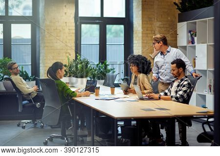 Office Life. Group Of Young Multiracial People Sitting At The Table In Coworking Space And Working T