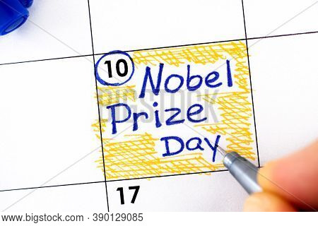 Woman Fingers With Pen Writing Reminder Nobel Prize Day In Calendar. December 10.