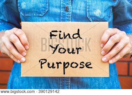 Woman Hands Holding Piece Of Cardboard With Words Find Your Purpose Against Brick Wall Background.