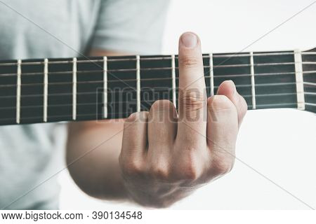 Close-up Chord On The Guitar Looks Like Fuck. Middle Finger Gesture. Adult Difficulties In Music Edu