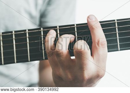 Guitarists Hand Playing An Major Barre Chord On The Fretboard Of An Classical Guitar.