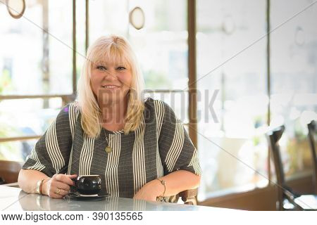 Beautiful Plus Size Woman Drinking Coffee At Vegan Cafe. Portrait Of Mature Woman In A Cafeteria Dri