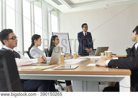 Asian Corporate Executive Facilitating A Discussion During Team Meeting In Office
