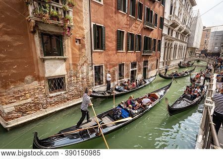 Venice, Italy - Sep 13, 2015: Many Gondoliers And Tourists On The Gondolas, Typical Venetian Rowing