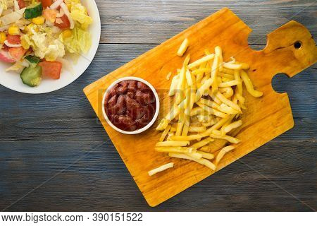 French Fries With Ketchup On Grey Blue Wooden Background. French Fries On Brown Wooden Plate With Ve