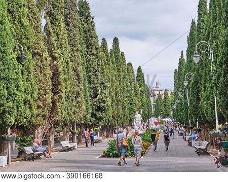 Yalta, Russia - September 19, 2020: People Walk Along Cypress Alley And Relax On Benches. Spa Town S
