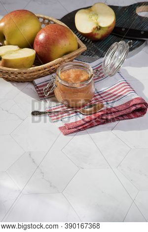 A Can Of Applesauce And Apples In A Wicker Plate On A Light Background, A Sliced Apple On A Wooden C