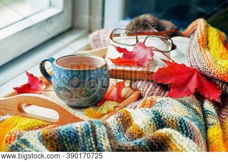 A сup Of Tea, A Book And Maple Leaves On The Wooden Windowsill. Autumn Concept.