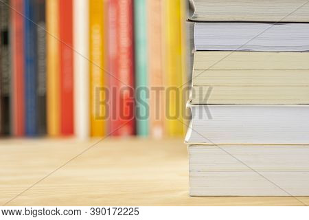 Pile Of Books In Front Of Unfocused Books Over A Wooden Table.